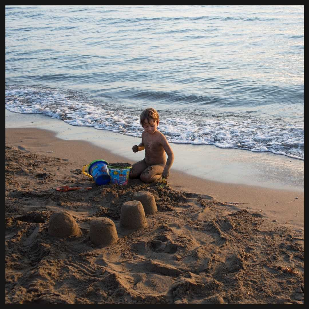 Young girl child making sandcastles at the beach